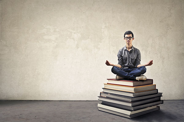 Young man sitting on books meditating