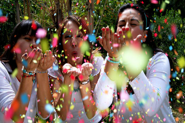 Three ladies blowing confetti into the air
